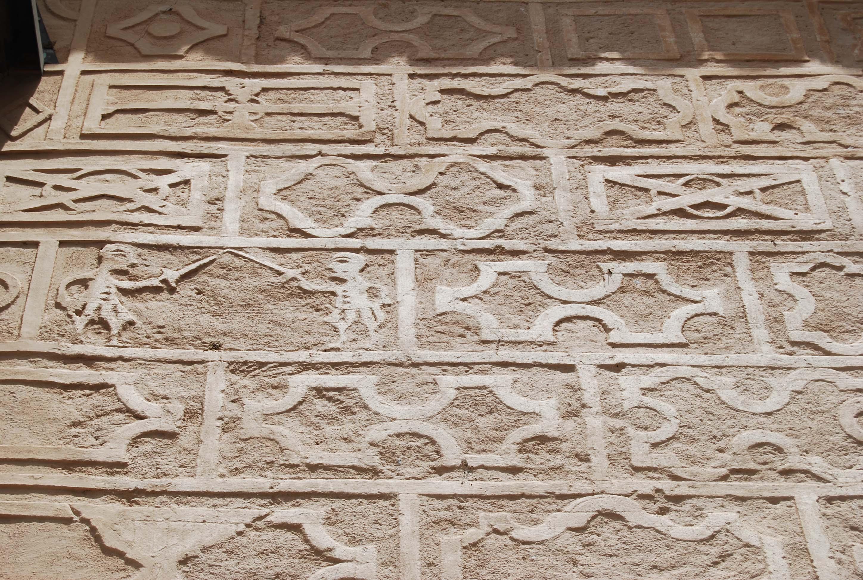 Detalle de la decoración esgrafiada con motivos antropomorfos en la misma pared exterior de la cabecera. © Fotografía: Alfonso Ruiz